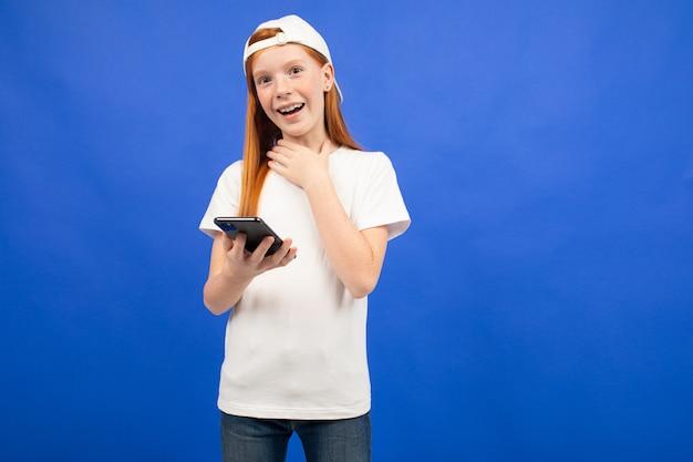 Verrast roodharige tiener meisje in een wit t-shirt met een gadget voor communicatie in handen blauw