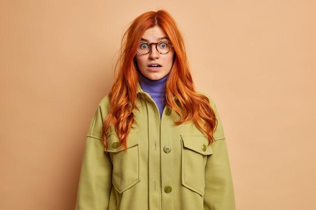Verrast roodharige vrouw kijkt met verwondering adem in van verbazing kan niet geloven in schokkende relevantie gekleed in groene jas.