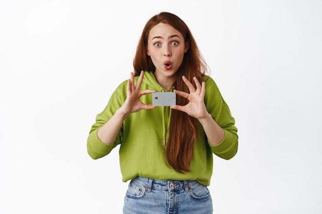 Verrast roodharige vrouw maakt aankondiging met creditcard, gaat winkelen, betalen voor iets contactloos, staande op wit