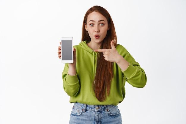 Verrast roodharige vrouw wijzende vinger naar smartphone-app, hijgend van ontzag, interessante applicatie op mobiele telefoon op wit tonen