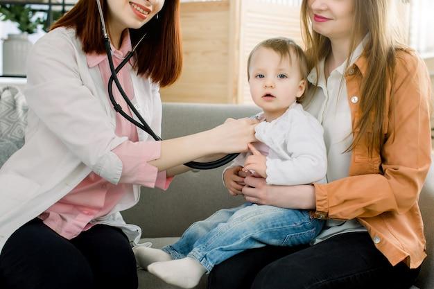 Verrast schattig babymeisje wordt gecontroleerd door een vrouwelijke arts met behulp van een stethoscoop in de kliniek