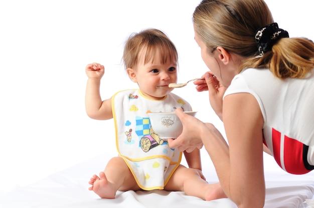 Verrast schattig klein babymeisje eten van lepel. moeder houdt bord vast en voedt kind. geïsoleerd op witte achtergrond