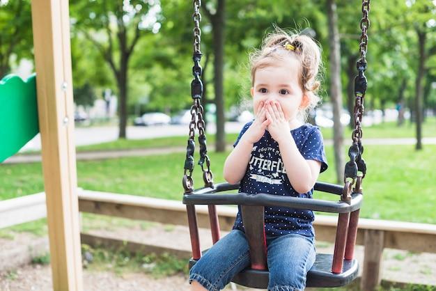Verrast schattig klein meisje, zittend op de schommel