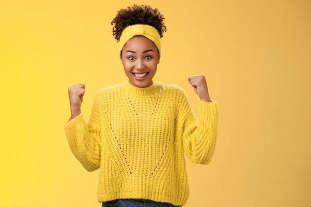 Verrast schattig teder afrikaans-amerikaans meisje kan niet geloven dat de prijsloterij gebalde vuisten triomfeert en glimlacht, wijd verwijde ogen onder de indruk verbaasd vieren van succes, overwinning gele achtergrond.