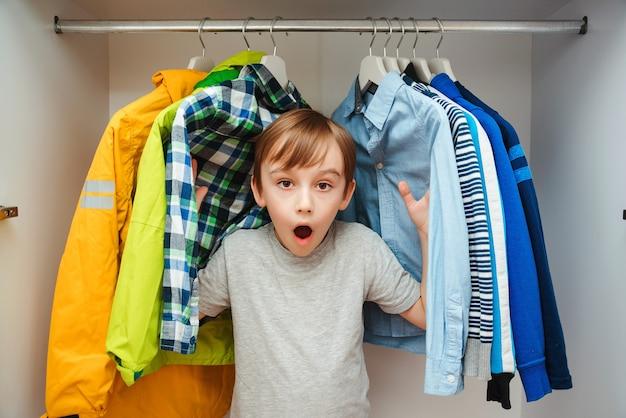 Verrast schattige jongen op zoek naar kleding in een kast