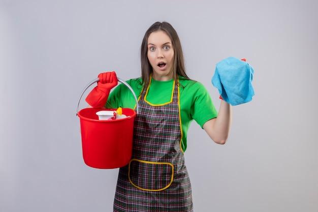 Verrast schoonmakend jong meisje die uniform in rode handschoenen dragen die schoonmakende hulpmiddelen en doek op geïsoleerde witte achtergrond houden