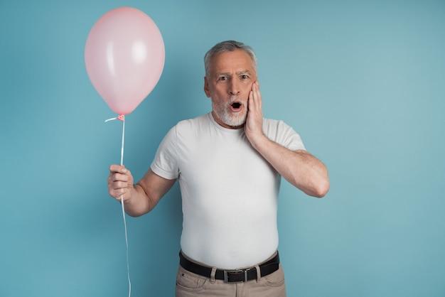 Verrast senior man met een roze bal in zijn hand.