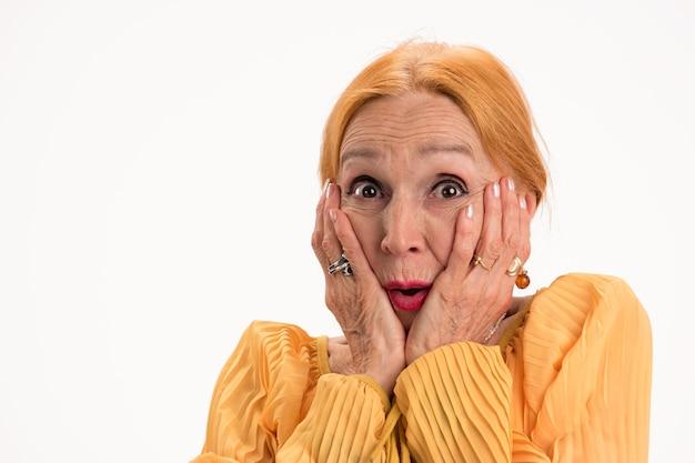 Verrast senior vrouw geïsoleerde dame met handen op gezicht zien en geloven?