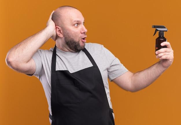 Verrast slavische mannelijke kapper van middelbare leeftijd in uniform vasthouden en kijken naar waternevelfles hand zetten achter hoofd geïsoleerd op oranje muur