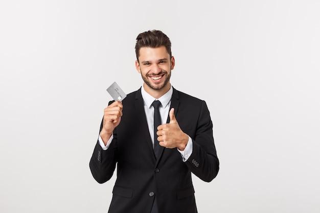 Verrast, sprakeloos en onder de indruk knappe blanke zakenman in klassieke pak met creditcard, zeg wauw, verbaasd staan