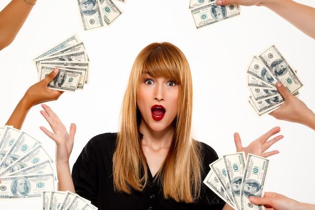 Verrast succesvolle zakenvrouw onder geld over witte muur