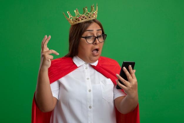 Verrast superheld vrouw van middelbare leeftijd dragen kroon met glazen houden en kijken naar telefoon geïsoleerd op groen