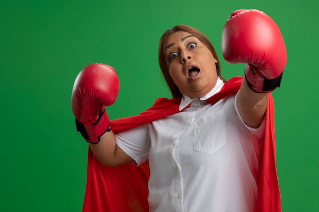 Verrast superheldwijfje dat van middelbare leeftijd bokshandschoenen draagt die handen uithouden die op groen worden geïsoleerd