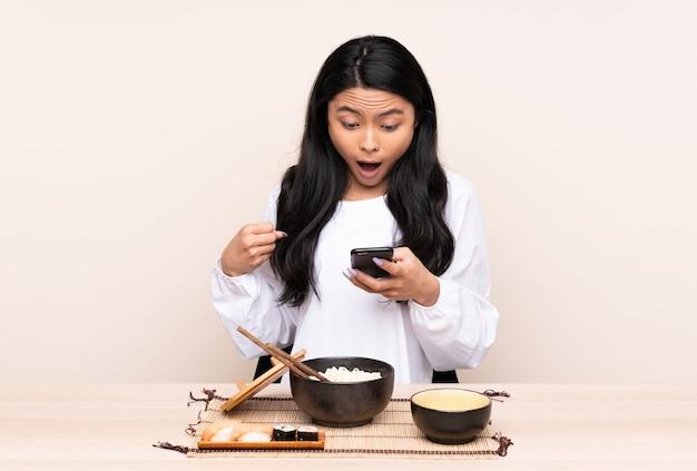 Verrast tiener aziatisch meisje die aziatisch voedsel op beige muur eten en een bericht verzenden