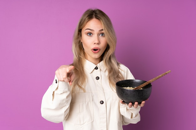 Verrast tiener russisch meisje op purpere muur en richtend voorzijde terwijl het houden van een kom noedels met eetstokjes