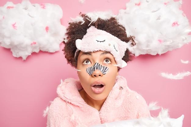 Verrast tienermeisje draagt reinigingsstrip op neus om poriën te ontstoppen wil een heldere, gladde huid draagt slaapmasker op voorhoofd nachtkleding omgeven door veren vormt binnen