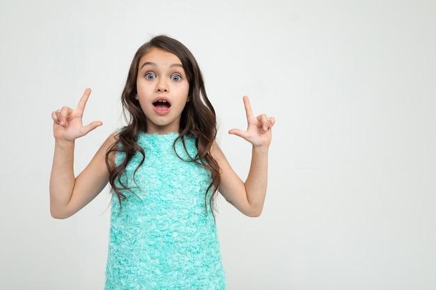 Verrast tienermeisje in een blauwe jurk duimen omhoog op een advertentie op een witte studio achtergrond.