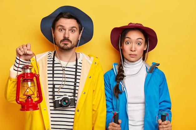 Verrast toeristenpaar heeft recreatietijd in de natuur, reist te voet, staat met wandelstokken, olielamp voor bliksem in de duisternis, staat dicht bij gele muur