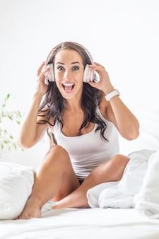 Verrast uitdrukking van een jonge vrouw zittend op een bed luisteren naar de muziek.