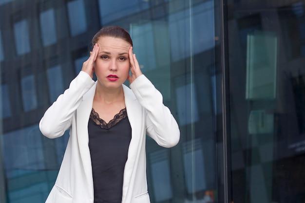 Verrast uitgeput moe zakenvrouw lijden aan hoofdpijn of migraine, hoofd met handen houden, camera buiten kijken. ziek op het werk, stressvolle baan. ontslagen. overbelaste vrouw in jas.