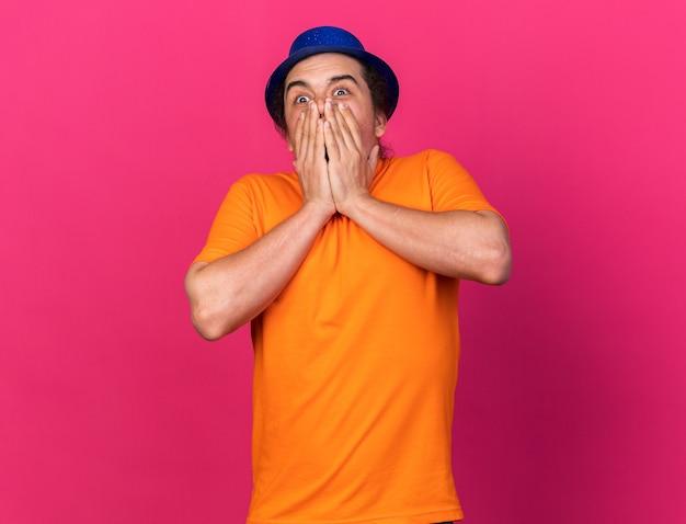 Verrast uitziende camera jonge man met feestmuts bedekt gezicht met handen geïsoleerd op roze muur