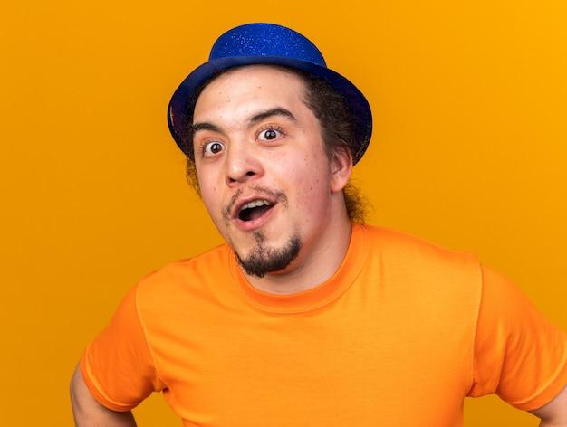 Verrast uitziende camera jonge man met feestmuts geïsoleerd op oranje muur