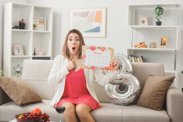 Verrast uitziende vrouw op gelukkige vrouwendag met kalender zittend op de bank in de woonkamer