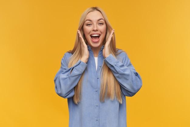 Verrast uitziende vrouw, verbaasd meisje met lang blond haar. het dragen van een blauw shirt. mensen en emotie concept. ik kan de opwinding niet vasthouden. kijken naar de camera, geïsoleerd op oranje achtergrond