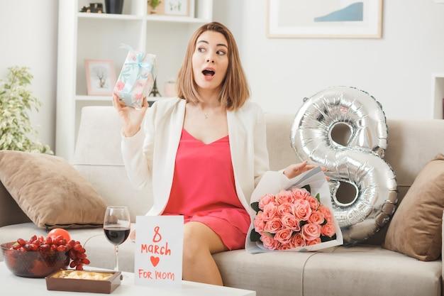 Verrast uitziende zijvrouw op een gelukkige vrouwendag met een cadeautje zittend op de bank in de woonkamer