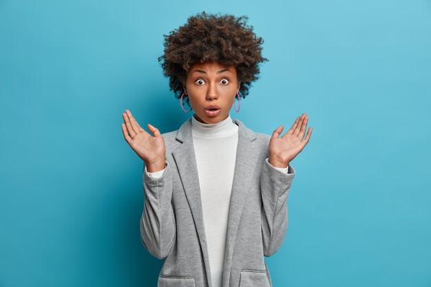 Verrast verbijsterde vrouw met donkere huid spreidt haar handpalmen, reageert op verbazingwekkend nieuws, beseft dat ze een belangrijke taak is vergeten, draagt een elegant grijs jasje
