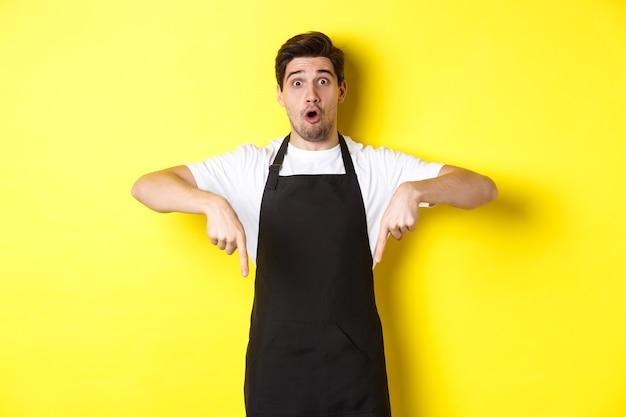 Verrast verkoper in zwart schort wijzende vingers naar beneden, kijkend verbaasd naar de camera, staande op gele achtergrond.