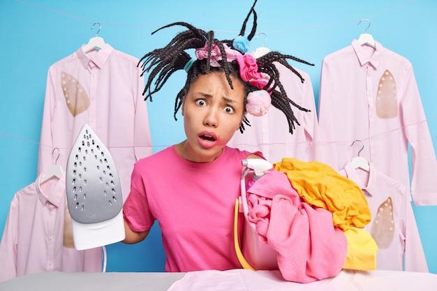 Verrast verontwaardigde donkere vrouw heeft grappige kapsel poses met stapel wasgoed gaat strijken doet huishoudelijk werk poses in de buurt van strijkplank tegen blauwe muur