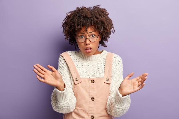 Verrast verontwaardigde vrouw met krullend haar heeft gespreide handen, kijkt geschokt naar de camera, draagt een ronde bril