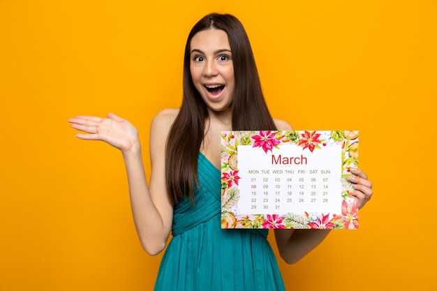 Verrast verspreidende hand mooi jong meisje op gelukkige vrouwendag met kalender