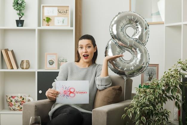 Verrast verspreidende hand mooie vrouw op gelukkige vrouwendag met ansichtkaart zittend op een fauteuil in de woonkamer