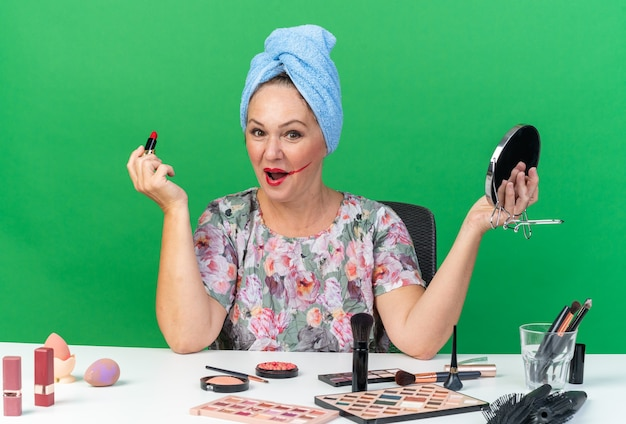 Verrast volwassen blanke vrouw met gewikkeld haar in een handdoek zittend aan tafel met make-up tools met lippenstift en spiegel geïsoleerd op groene muur met kopieerruimte