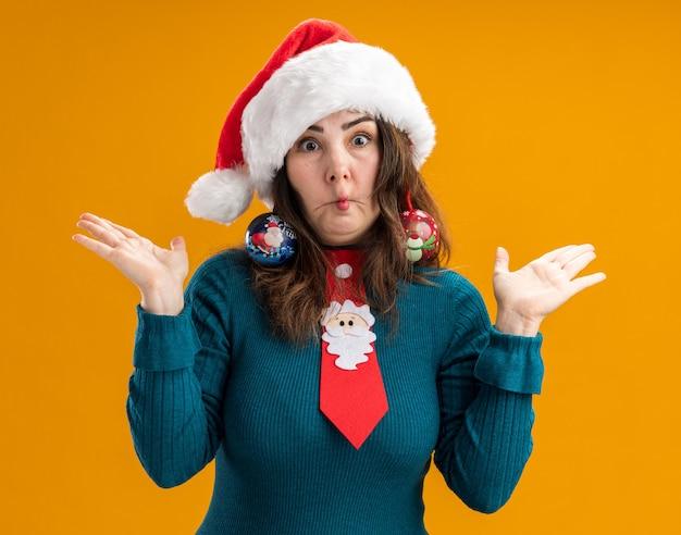 Verrast volwassen blanke vrouw met kerstmuts en kerstman stropdas houdt glazen bol ornamenten op oren vis mond maken en handen open houden geïsoleerd op een oranje achtergrond met kopie ruimte