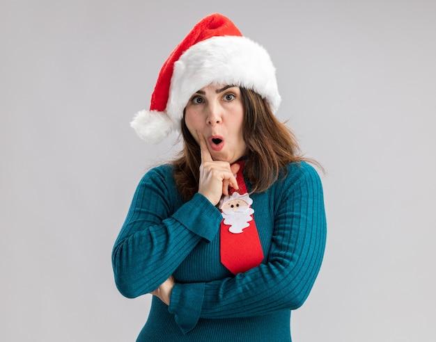 Verrast volwassen blanke vrouw met kerstmuts en kerststropdas houdt kin geïsoleerd op een witte muur met kopieerruimte
