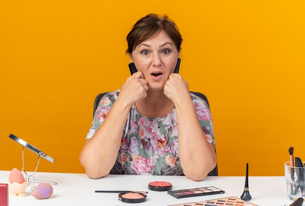 Verrast volwassen blanke vrouw zittend aan tafel met make-up tools houdt make-upborstels vast