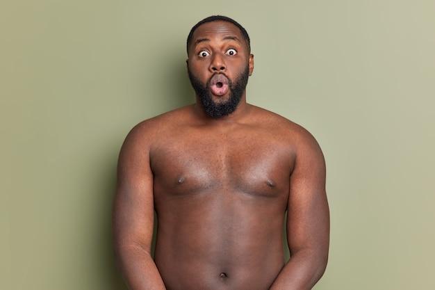Verrast volwassen man met baard staat shirtless staart naar voren houdt mond wijd open reageert op iets onverwachts en geschokt geïsoleerd over studio muur van kaki kleur