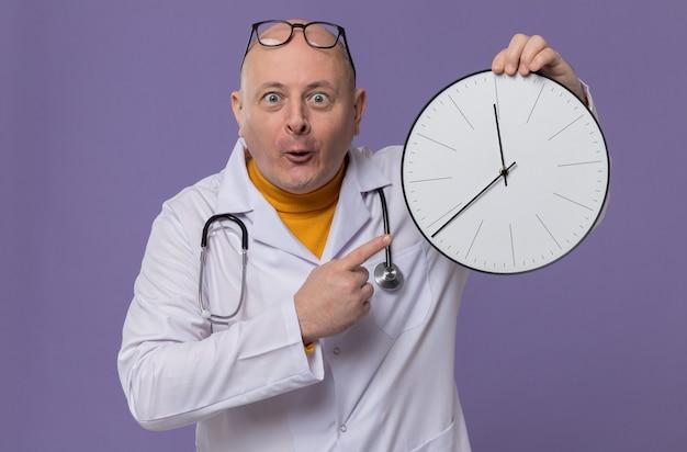 Verrast volwassen man met bril in doktersuniform met stethoscoop vasthouden en wijzend op de klok
