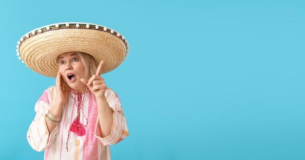Verrast volwassen mexicaanse vrouw in sombrerohoed op kleur oppervlak