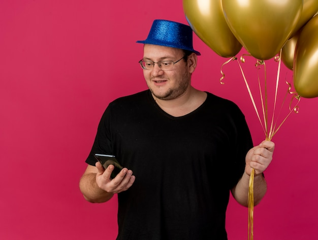 Verrast volwassen slavische man in optische bril met blauwe feestmuts houdt heliumballonnen vast en kijkt naar de telefoon