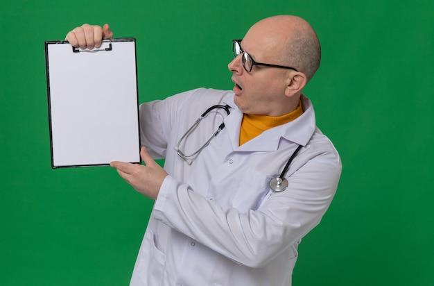 Verrast volwassen slavische man met optische bril in doktersuniform met stethoscoop vasthouden en kijken naar klembord