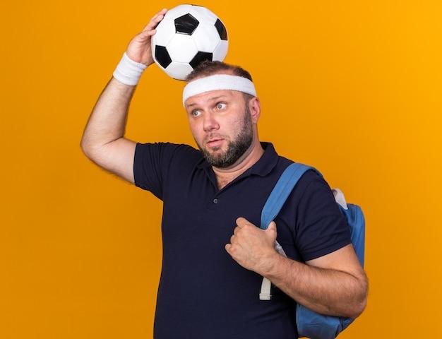 Verrast volwassen slavische sportieve man met rugzak hoofdband en polsbandjes bal boven het hoofd kijken naar kant geïsoleerd op oranje muur met kopie ruimte