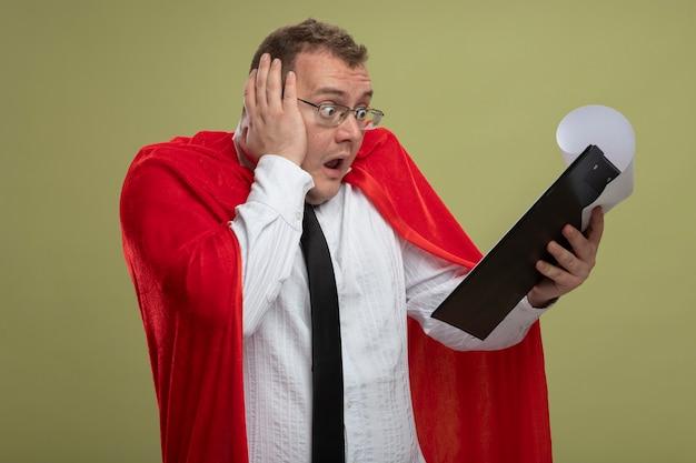 Verrast volwassen slavische superheld man in rode cape bril en stropdas houden en kijken naar klembord hand op het hoofd zetten geïsoleerd op olijfgroene achtergrond