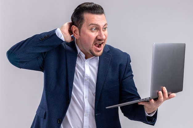 Verrast volwassen slavische zakenman die laptop vasthoudt en bekijkt die op een witte muur met kopieerruimte wordt geïsoleerd