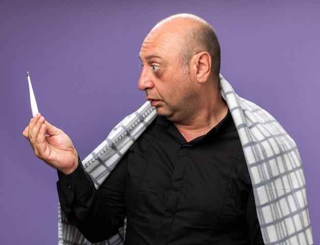 Verrast volwassen zieke blanke man gewikkeld in geruite houden en kijken naar thermometer geïsoleerd op paarse muur met kopieerruimte