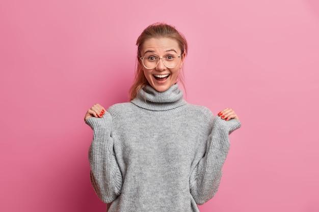 Verrast vreugdevolle jonge europese vrouw steekt handen op en kijkt met opwinding iets uitstekends