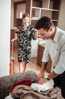 Verrast vriendin. vriendin voelt zich verrast om haar man zijn koffer alleen te zien uitpakken